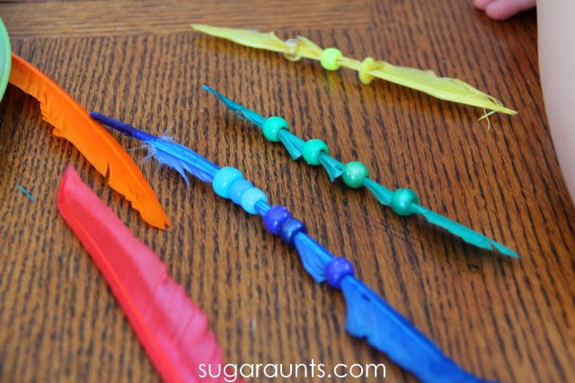 Threading colored beads on feathers is a great way for prechoolers and toddlers to work on colors and fine motor skills.
