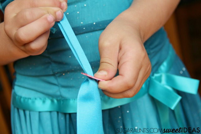 How to teach a child to zip a coat using a ribbon and a bread tie.